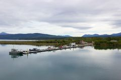 Boats docked in quiet mountain lake, Yukon, Canada. On a calm, cloudy day, a row of boats along a dock are reflected in the still waters of a lake, with the Stock Photography