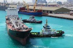 Boats docked to industrial ship in port Stock Photography