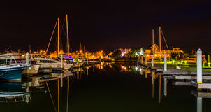 Boats and docks reflecting in the water at night, at a marina on Royalty Free Stock Photos