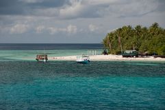 Boats Doni near a small islet in the water area of the Indian Ocean, Maldives. Boats Doni near small islet in the water area of the Indian Ocean, Maldives Royalty Free Stock Image