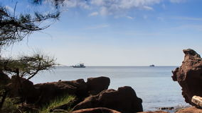 Boats Drift along Skyline Rocks on Beach at Foreground. Boats drift along skyline at foreground rocks and tropical pine on beach against sky and clouds stock footage