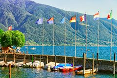 Boats at embankment in Ascona in Ticino in Switzerland CH. Ascona, Switzerland - August 23, 2016: Boats at the embankment of the luxurious resort in Ascona on royalty free stock photo