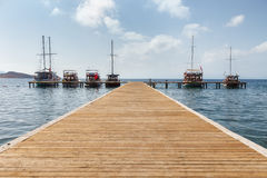 Boats at the end of the pier on the sea Stock Photography