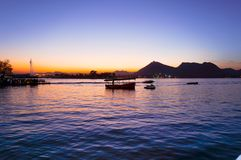 Boats on pichola lake at dusk with mountains in the distance Royalty Free Stock Image