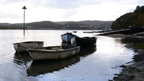 Boats feathered and floating near sandy shore stock video
