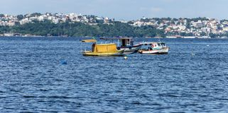 Boats Fishing boats Fishermen Sunny day Sea and mountain Blue sea Sea and trees Stock Image