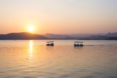 Boats floating on Lake Pichola with colorful sunset reflated on water beyong the hills. Udaipur, Rajasthan, India. Boats floating on Lake Pichola with colorful Royalty Free Stock Photo