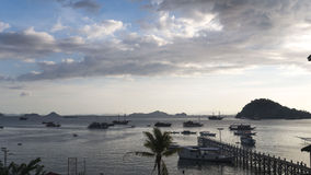 Boats floating at sunset in harborr. Various boats float on the water in the harbor of a port island. A few small hilly islands sit on the horizon, the sun Stock Photo