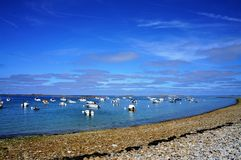 Boats floating in the water near a pebbles beach in Brittany stock photos