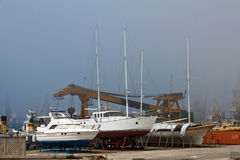 Boats in fog. Yachts on land in foggy weather stock image