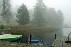 Boats in the fog near the shore. Boats in the fog at the shore tied to the pier stock photo