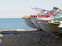 Boats on the foreshore. The prows of four colorful boats pulled up on a shingle beach, background tranquil blue sea and pale blue sky stock image