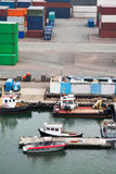 Boats and freight containers in cargo port Royalty Free Stock Photo
