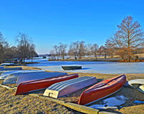 Boats and frozen lake. A bright blue sky over a frozen lake with boats lying on the shore Stock Images