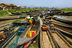 Boats gathered for market in Inle lake, Myanmar. Nyaungshwe, Myanmar - April 24, 2016: Many boats gathered for Nam Pan outdoor market on Lake Inle. Many people Stock Image