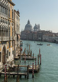 Boats & gondolas on grand canal in Venice. Water taxi and gondola on the grand canal in Venice in front of the Basilica di Santa Maria della Salute stock photos