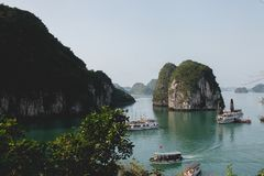 Boats in Halong Bay. Among limestone islands topped by rainforests in emerald water. World heritage seascape Royalty Free Stock Photography