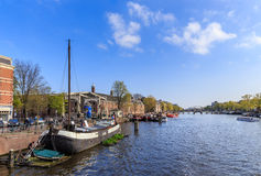 Boats in harbor on the canal in Amsterdam Stock Photos