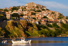 Boats in the harbor with castle on the hill at Molyvos Greece. Twilight at the seaside town of Molyvos on the island of Lesvos in Greece stock images