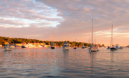 Boats in the harbor at dusk. Boothbay Harbor boats reflected in the water at dusk Stock Photo