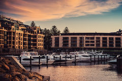 Boats in harbor at dusk. Surrounded by hotels and bars Stock Photo