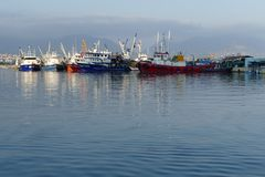 Boats in a harbor. Fishing boats in a harbor, reflecting in the deep blue sea water stock photography