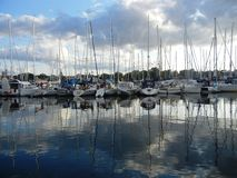 Boats in a harbor mirrored on water surface stock photos