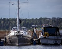 Some boats in the harbor. Boats in the harbor waiting to sail of. Sailing boat and a motorboat side by side royalty free stock photography