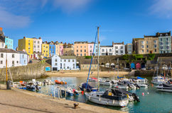 Boats in Harbour in Tenby and Blue Sky. Small Harbour Lined with Pastel Coloured  Old Buildings in Tenby, Wales, on a Sunny Spring Day Royalty Free Stock Image