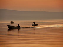 Boats in haze and sunset. Tree fishing boats with fishermans  in the sunset and the haze at Adriatic sea (Croatia - dalmatia) . Horizontal color photo Stock Photos