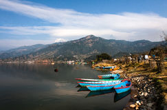 Boats on Himalayan lake. A perfect day at the lake in Pokhara, with the Annapurna massive in the background Stock Photos