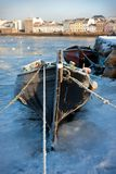 Boats in ice on the bank of river Royalty Free Stock Photography