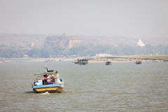 Boats on the Irrawaddy River. The Mingun Pahtodawgyi pagoda is visible in the background, focus on foreground, Mingun, Sagaing Region, Burma, Myanmar royalty free stock images
