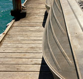 Boats on a jetty. Dinghys moored on a wooden pier Stock Photos