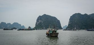 Boats at the jetty in Quang Ninh, Vietnam. Wooden boats docking on Ha Long Bay in Quang Ninh, Vietnam Stock Photos