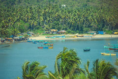Boats in a lagoon on a background of a sandy beach with palm trees Royalty Free Stock Image