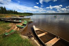 Boats by lake. Image of lake with some boats on the shore under cloudy sky stock photos