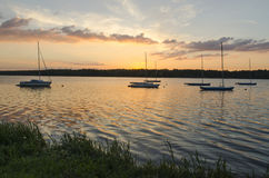 Boats in lake. At getting sun royalty free stock photography