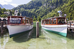 Boats on the lake. Konigssee. Germany. Two boats on the lake at the pier Stock Photos