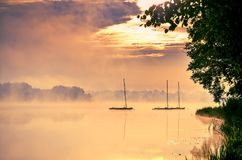 Boats on the lake. Morning foggy lake at sunrise royalty free stock image