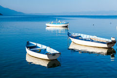 Boats on Lake Ohrid. This is a picture of three white and blue boats floating on a calm Lake Ohrid, Macedonia Royalty Free Stock Photography