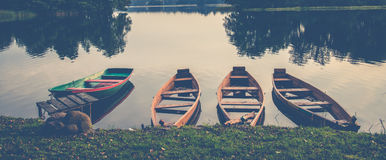Boats in a lake. Peaceful lake with four boats, soft color and banner or panorama format Royalty Free Stock Photo