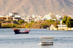 Boats on lake pichola with the city of Udaipur in the background. Ornate boats on the blue waters of lake pichola with the city of Udaipur in the background Stock Photography
