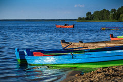 Boats on the lake shore in summer. Rowing boats parked on the lake shore, with a man rowing in the background Stock Photo