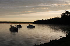 Boats on a lake at sunrise Stock Photography
