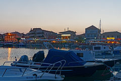 Boats in Lefkada Harbour, Greece. Modern recreational boats moored in the harbour at Lefkada, an Ionian Greek island, Greece, at dusk, with waterfront tavernas royalty free stock images