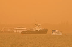 Boats lie at anchor in a dust storm over the ocean. Boats lie at anchor in a dust storm in a seaside bay. It has blown in by winds from inland dry inland areas Stock Images