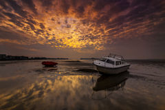 Boats lie high and dry on the shore at Sandbanks Stock Photos