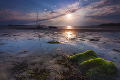 Boats lie high and dry on the shore at Sandbanks Stock Images