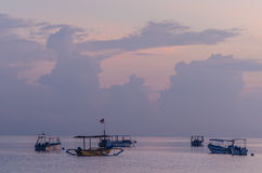 Boats in the lilac colored sunrise. At the sea royalty free stock photography